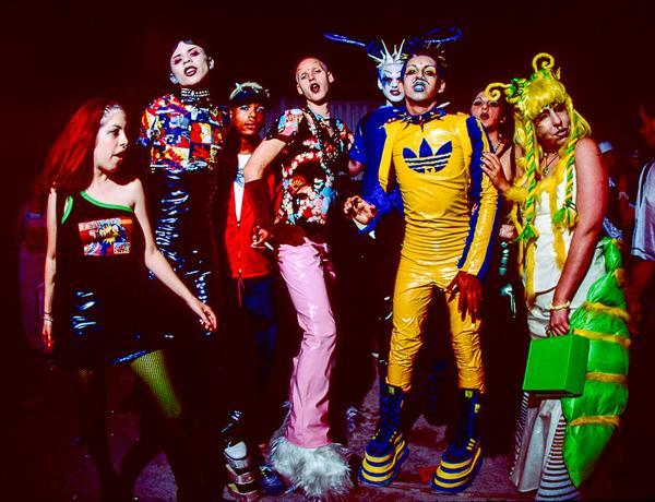 Gente de estética Club Kid, con latex coloridos y piercings mirando a cámara